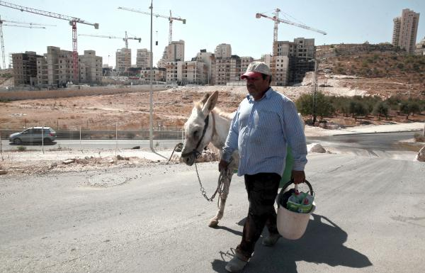 A Palestinian man walks near a construction site for new Israeli housing in the East Jerusalem neighborhood of Har Homa in September. The Palestinians claim East Jerusalem as a capital of a future state and object to Israeli building in the eastern part of the city and throughout the West Bank. Israel claims all of Jerusalem as its capital.