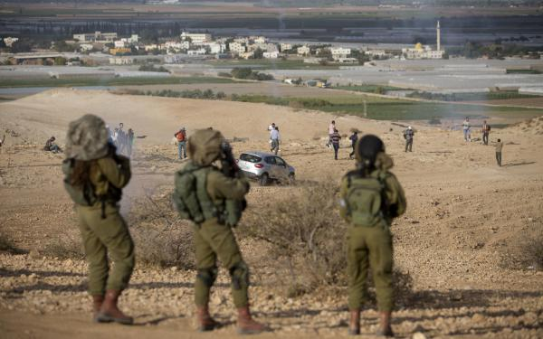 Palestinians and Israeli activists run away from tear gas fired by Israeli soldiers during a demonstration against the construction of Jewish settlements in the Jordan Valley, in the West Bank, on Nov. 17.