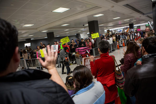 Demonstrators cheer passengers exiting international flights at Washington Dulles International Airport in D.C.