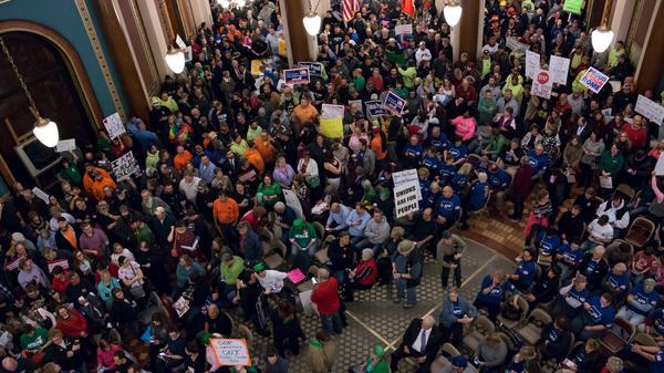 Hundreds of demonstrators on the Iowa Capitol's Rotunda floor protest a bill that would restrict collective bargaining for local and state government workers.
