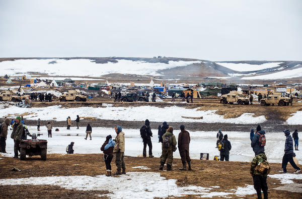 Protestors stand on the southern bank of the Cannonball River, on reservation land, as police secure the remainder of the Oceti Sakowin camp on the opposite bank.