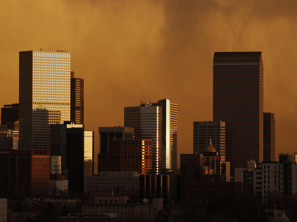 Smoke from wildfires in Colorado hangs over the Denver skyline at sunrise on Monday.