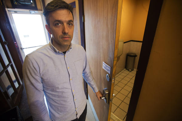 1369 Coffee House owner Josh Gerber opens the bathroom door which has a combination lock given to patrons at the front counter. (Jesse Costa/WBUR)
