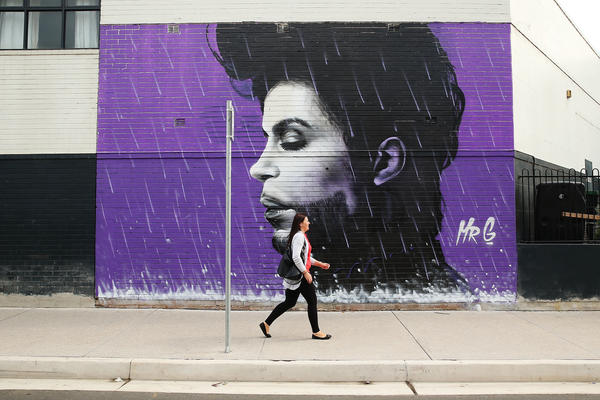 A woman walks past a mural of Prince on April 28, 2016 in Sydney, Australia.