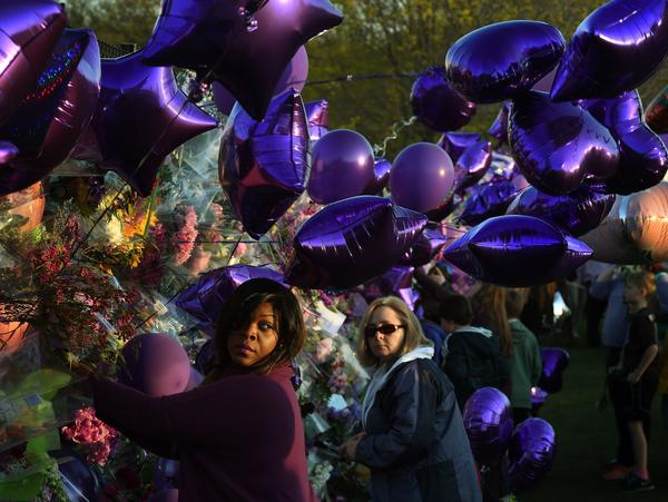 Prince fans pay their respects at a memorial wall outside the Paisley Park compound of music legend Prince in Minneapolis, Minn., on April 22, 2016.