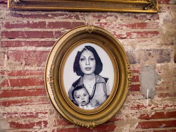 This photo on the wall of Lapis shows Shamim Popal holding her daughter, Fatima, who was 6 months old when the family fled Afghanistan after the Soviets invaded in 1979. This was Shamim Popal's passport photo.
