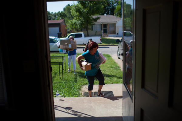 Often when families transition from the local shelter to permanent housing, the Family Support Staff help provide items for the home. Here, Jenn Mars (left), the former director of Family Support at Positive Tomorrows, helps Jackie (front) move into their new home before her two boys get home from school.
