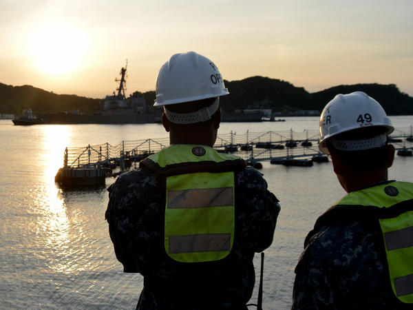 Sailors watch pier-side as the Arleigh Burke-class guided-missile destroyer USS Fitzgerald (DDG 62) returns to Fleet Activities (FLEACT) Yokosuka following a collision with a merchant vessel while operating southwest of Yokosuka, Japan.