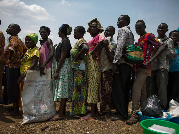 Families wait for a food aid delivery at Uganda's Bidi Bidi refugee camp in February. Bidi Bidi is home to more than 270,000 people who have fled South Sudan's civil war and is the biggest refugee camp in the world.