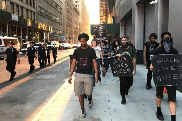Mike Bento (center), an organizer with NYC Shut It Down, leads a march in honor of a black transgender person who was recently killed in New York City.