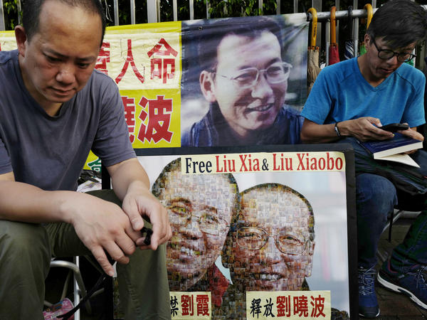 Protesters display portraits of jailed Chinese Nobel Peace Prize laureate Liu Xiaobo outside the Chinese liaison office in Hong Kong on Wednesday. Liu has expressed the wish to leave China for medical treatment, but the government has refused.