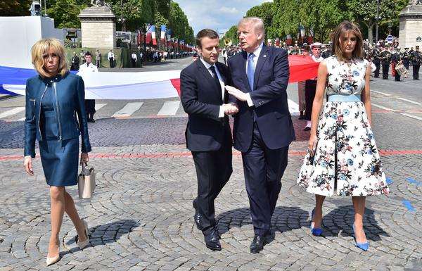 French President Emmanuel Macron and President Trump share a handshake as they walk next to Macron's wife, Brigitte Macron, and U.S. first lady Melania Trump at Friday's Bastille Day parade in Paris.