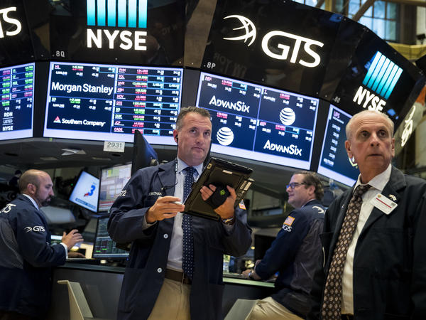 Traders and financial professionals work on the floor of the New York Stock Exchange on Tuesday. Major stock indexes are in record territory.