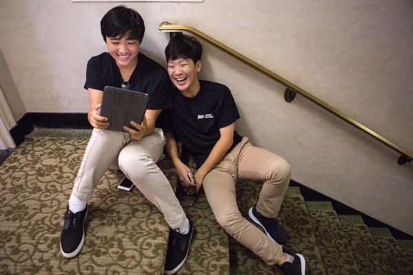 Taking a break, Youngmo Koo (left) and Ryan Lee of South Korea pass the time with a video game.