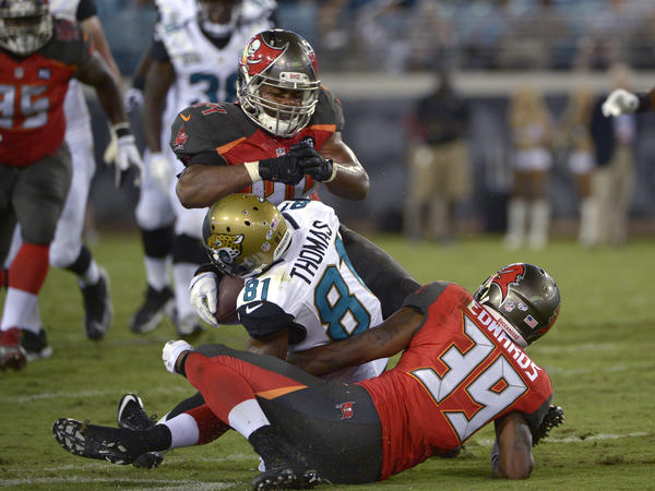 Jacksonville Jaguars wide receiver Lamaar Thomas (center) is hit in the head by Tampa Bay Buccaneers linebacker Brandon Magee as cornerback Kip Edwards helps make the tackle a 2014 preseason game. Magee was penalized for the hit.