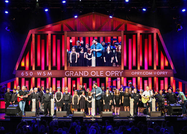 "Campers with Williams syndrome on stage at the Grand Ole Opry performing their original song, ""I Love Big,"" with country artist Chris Young in front of a crowd of thousands."