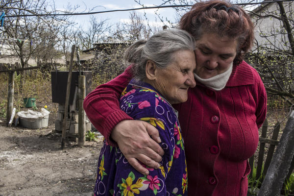 Raya Shaporova, 70, (left) a local resident who has not left despite the dangers of fighting all around, gets a hug from Vera Anoshina, 52, who lives nearby.