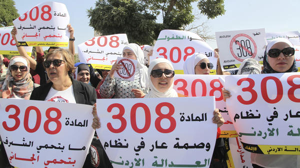 "Activists protest in front of Jordan's parliament in Amman on Tuesday, as legislators voted to repeal a provision that allows a rapist to escape punishment if he marries his victim. The banner in the middle reads, ""Article 308 is a disgrace in the Jordanian justice system."" The banner on the left says ""Article 308 does not protect honor, it protects the culprit."""