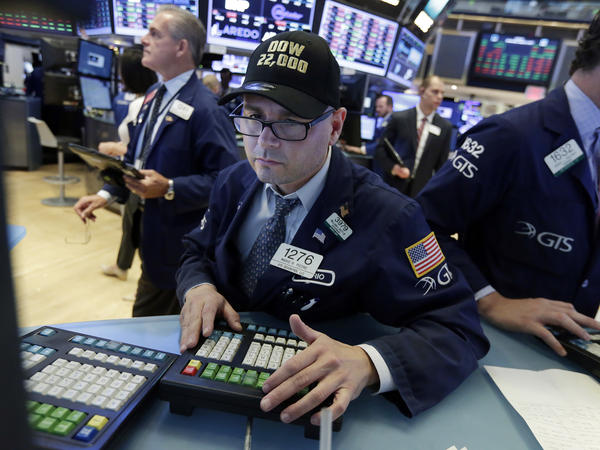 """Mario Picone, a specialist at the New York Stock Exchange, wears a """"Dow 22,000"""" as he works at his post on the exchange floor."""