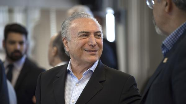 Brazilian President Michel Temer flashes a smile during a meeting in Rio de Janeiro on Sunday. The embattled leader has been one of the subjects of a vast, yearslong corruption probe that has snared many of the country's most powerful politicians and business people.