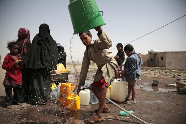 A boy rinses a bucket as he and others collect water from a well that is allegedly contaminated with cholera bacteria, on the outskirts of Sanaa, Yemen.