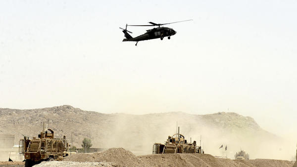 An American helicopter hovers over a NATO convoy struck by a suicide bomb Wednesday. The Pentagon says the attack, which unfolded near the southern Afghan city of Kandahar, killed two U.S. service members.