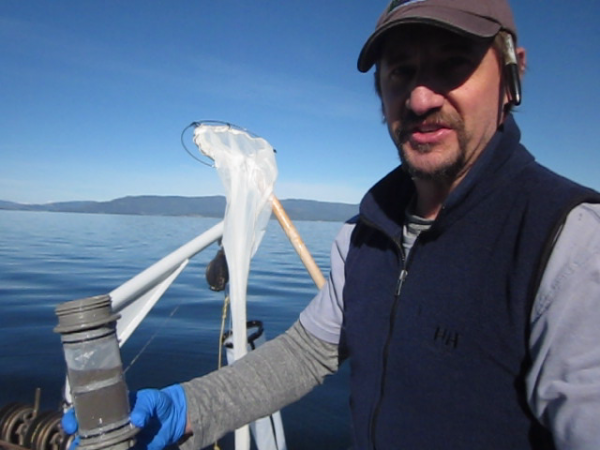 Phil Matson collects a water sample from Flathead Lake for use in e-DNA testing for quagga and zebra mussels.