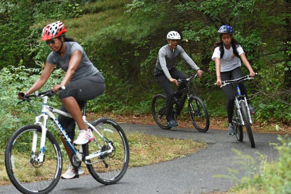 President Barack Obama rides bikes with his wife, Michelle, and daughter, Malia, on Martha's Vineyard in August 2015.