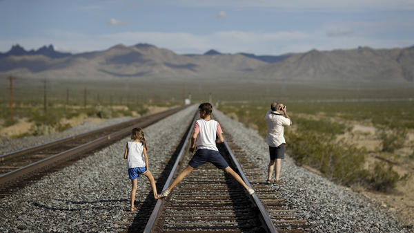 One of the nation's largest cannabis companies announced it has bought the entire 80-acre California desert town of Nipton. A family walks along train tracks in the town on Thursday.