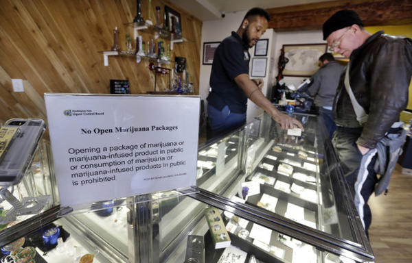 <p>Cannabis City clerk Will Bibbs, left, helps a customer looking over a display case of marijuana products at the shop in Seattle.</p>
