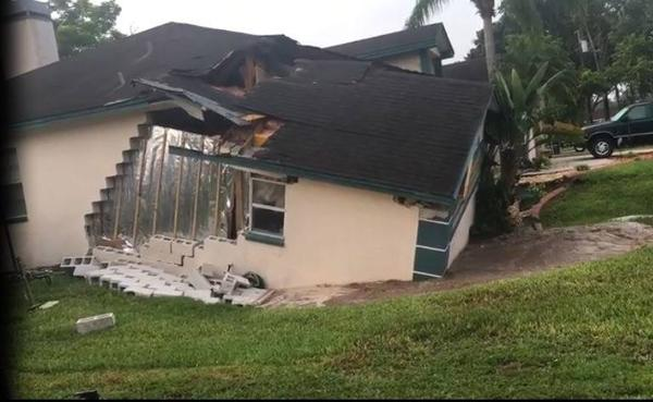 In this image taken from a YouTube video, the first house swallowed by a Pasco County sinkhole July 14 cracks apart.