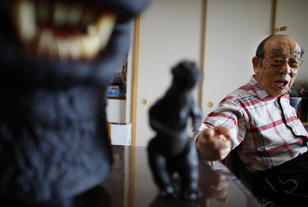 Original Godzilla actor Haruo Nakajima points a figure of the monster he made for the movie during a 2014 interview at his home in Sagamihara, near Tokyo.