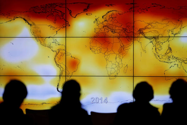 Participants look at a world map showing climate anomalies during the World Climate Change Conference 2015 in France. A draft government report on climate, which was released by <em>The New York Times</em> ahead of publication, says the U.S. is already experiencing the consequences of global warming.