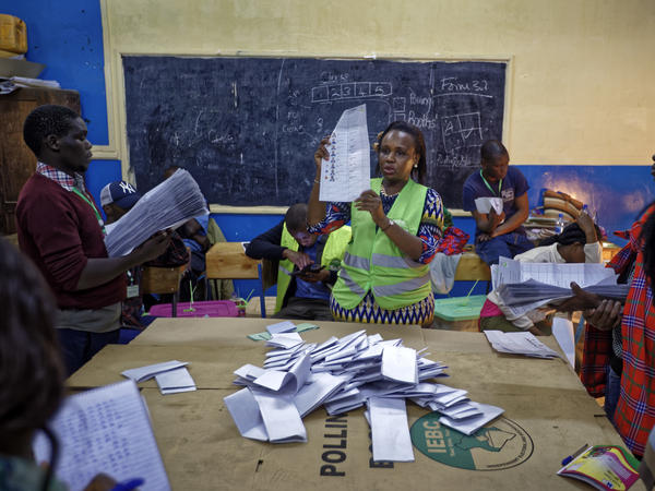 An electoral counting officer counts votes while others hold the piles of ballots counted for each candidate, at a polling station in Nairobi, Kenya, on Tuesday.