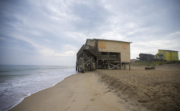 The Atlantic Ocean laps at the feet of a condemned house on Seagull Drive on Nags Head Beach on North Carolina's Outer Banks. The house was part of a larger development of houses that have either been moved or have succumbed to the ocean.  (Jesse Costa/WBUR)
