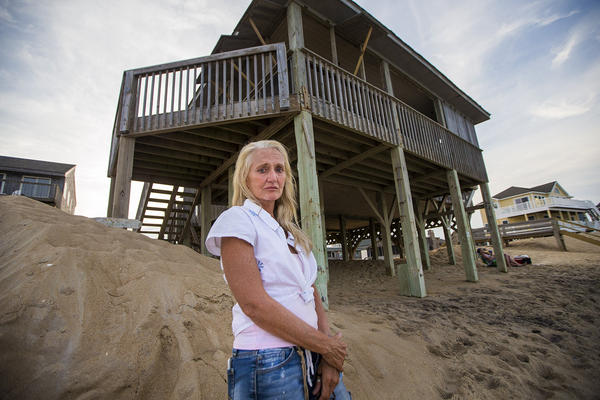 "Freve Pace stands in front of the house she once owned but had to sell because of the repeated storm damage and erosion of the beach. When she bought it in the 1990s, says says, ""There was a dune in front of it. We couldn't see the sea. It became clear we had to sell. I am still sad about it."" (Jesse Costa/WBUR)"