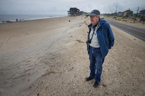 Stanley Riggs, of East Carolina University, stands on the edge of the Rodanthe Beach and Highway 12, where the Outer Banks are particularly prone to storm damage. (Jesse Costa/WBUR)