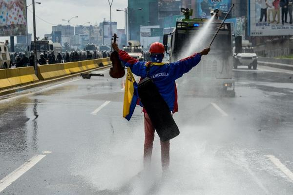 Opposition activist Wuilly Arteaga stands with a violin in front of an armoured vehicle of the riot police during a protest against President Nicolas Maduro in Caracas, on May 24, 2017. (Federico Parra/AFP/Getty Images)