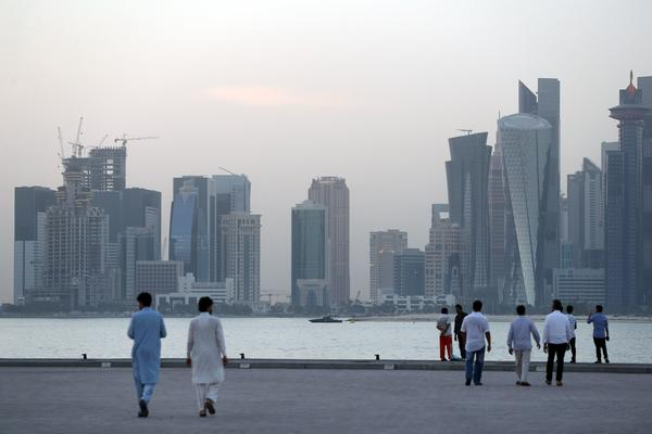 People walk on the corniche of Doha, Qatar on July 2. Visitors from 33 countries would be able to stay for up to 90 days in Qatar.