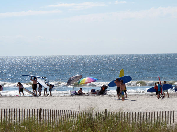 Surfers gather on the beach in Ocean City, N.J., in June of last year. A 52-year-old lifeguard who was fired by the city has won a $130,000 age-discrimination suit.