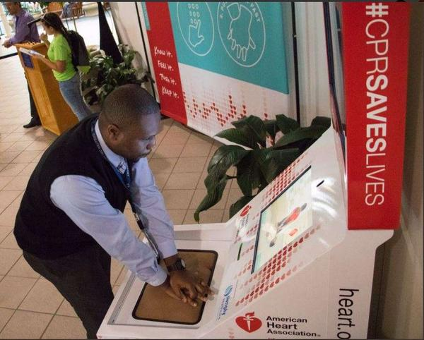 An airline employee uses the hands-only CPR kiosk at Orlando International Airport.
