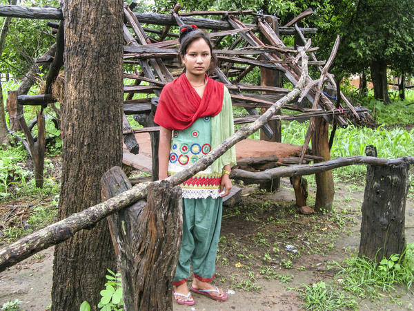 "Kamala stands in front of the hut where she sleeps when she has her period. She lives in western Nepal and was 14 when the photo was taken for an NPR story. She told us: ""I'm afraid of snakes and men."""