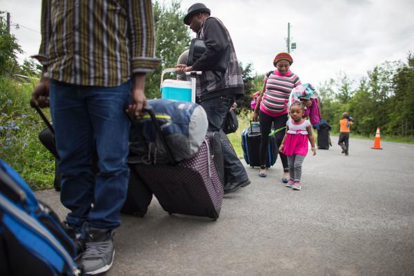 A long line of asylum-seekers waits to cross the Canada-U.S. border near Champlain, N.Y., on Sunday. The spike in new arrivals has overwhelmed existing Canadian facilities, and temporary housing is being arranged or assembled in Montreal and along the border.