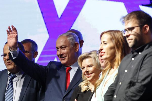 Israeli Prime Minister Benjamin Netanyahu (second from left) and his wife Sara (center) react during a gathering by Likud party members and activists at the Tel Aviv Convention Center on Aug. 9, 2017 in a mass show of support for the prime minister, who is facing a string of corruption investigations. (Jack Guez/AFP/Getty Images)