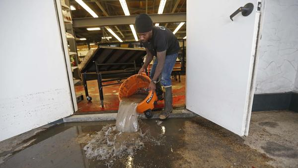 "Dwayne Boudreaux Jr., owner of the Circle Food Store in New Orleans, dumps out dirty water that was vacuumed up from the store on Monday, after severe flooding over the weekend. The city's pumps were not fully functional, officials now acknowledge. Boudreaux told <a href=""http://bit.ly/2fw9LaA"">a local news station</a> that the last time he saw waters rise so high was during Hurricane Katrina."