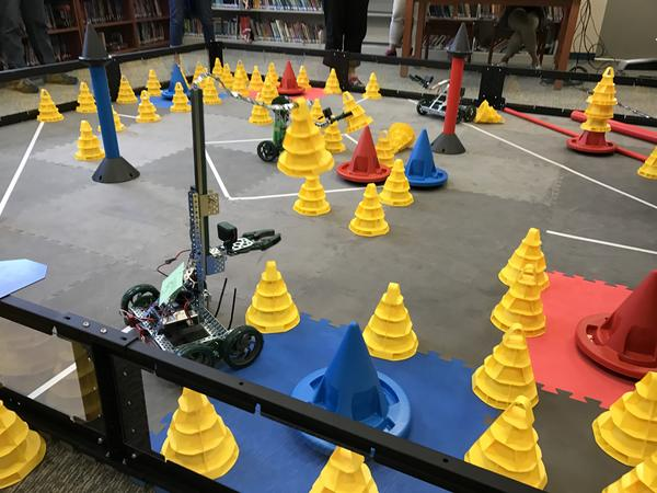 The teachers raced with their robots to gather and stack yellow cones within the designated competition space.