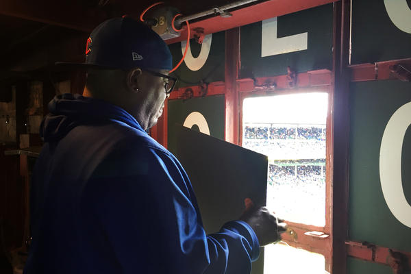 Veteran scoreboard operator Darryl Wilson changes a number on the scoreboard.