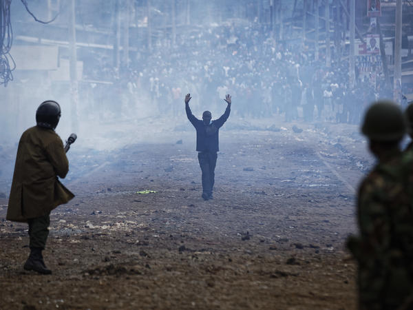 A man seeking safety walks with his hands in the air through a thick cloud of tear gas toward riot police, as they clash with protesters throwing rocks in the Kawangware slum of Nairobi, Kenya, on Thursday.