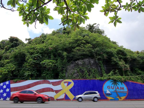Afternoon traffic passes in front of a wall painted with the flags of the U.S. and Guam in the Tumon district on the island of Guam on Friday. The island has become a talking point in the rhetoric coming from President Trump and North Korea.