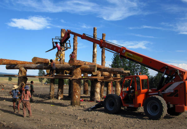 <p>A team uses an all-terrain crane to place a log crossbeam in place on one of the structures that make up the Solar Temple.</p>